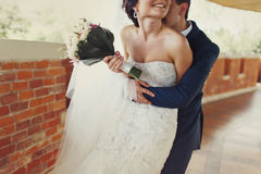Groom kisses back of bride's neck holding her from behind Stock Photo