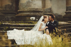 Groom kisses beautiful bride sitting on the old stone footsteps Stock Photo