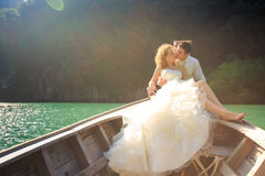 Groom kisses blonde bride in fluffy on nose of longtail boat. Groom kisses blonde curly bride in fluffy wedding dress sitting on nose of longtail boat against stock image