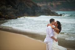 The groom kisses the bride against the sea rocks. couple in love on a deserted beach stock photo