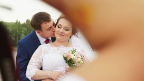 The groom kisses the bride on the cheek stock video footage