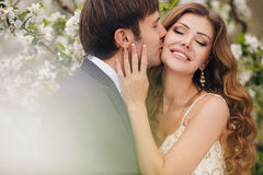 The groom kisses the bride in the flowered Park. Stock Image
