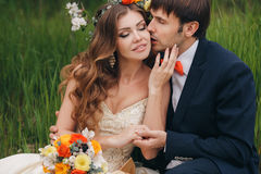 The groom kisses the bride in the flowered Park. Stock Photos