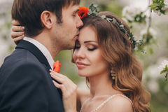 The groom kisses the bride in the flowered Park. Stock Images