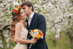 The groom kisses the bride in the flowered Park. Stock Photography