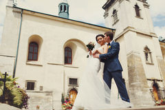 Groom kisses a bride in the front of old white cathedral Stock Photos