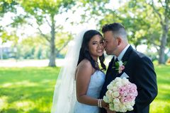 Groom kisses bride on her cheeks, Caucasian groom and Asian bride stock image