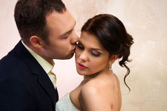 Groom Kisses Bride In Empty Room Stock Photography