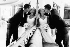 Groom kisses a bride leaning her to a wall behind a big mirror.  stock photography