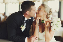 Groom kisses a bride leaning on the table Royalty Free Stock Photo