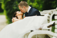 Groom kisses a bride while she lies in his hugs on the bench Stock Photo