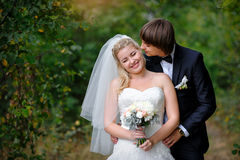 Groom kisses the bride in love in the summer park Stock Photos