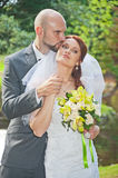 Groom kisses bride in park Royalty Free Stock Images