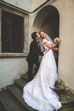 Groom kisses bride's cheek bending her over in the entrance Stock Photos