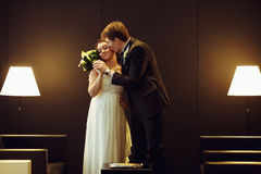 Groom kisses bride`s cheek holding her hand with a wedding bouqu Royalty Free Stock Image