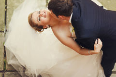 Groom kisses bride's neck while she looks up in the sky Royalty Free Stock Images