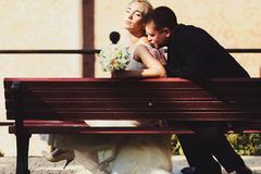 Groom kisses bride's shoulder while they rest in the sunrays on Royalty Free Stock Photography