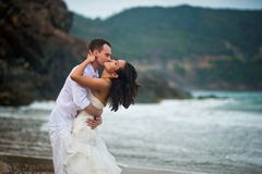 Groom kisses the bride at the sea. couple in love on a deserted beach stock photos