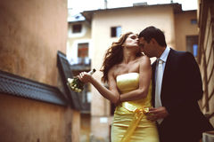Groom kisses bride softly while wind blows her hair. A Royalty Free Stock Photography