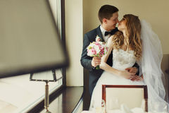 Groom kisses a bride standing behind a window.  Royalty Free Stock Images