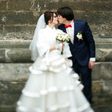Groom kisses a bride tender standing somewhere in the old city Royalty Free Stock Photography