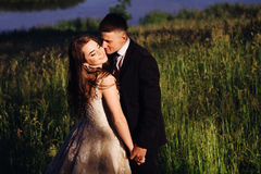 Groom kisses bride tender while she stands smiling Royalty Free Stock Photography