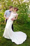 Groom kisses the bride on walk on their wedding day Royalty Free Stock Images