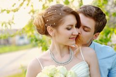Groom kisses the bride on walk on their wedding day Royalty Free Stock Photo