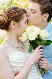 Groom kisses the bride on walk on their wedding day Royalty Free Stock Image