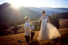 Groom kisses hand of bride. Sunset in the mountains on background. Stock Photos