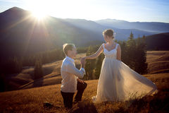 Groom kisses hand of bride. Sunset in the mountains on background. Royalty Free Stock Photos