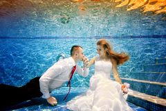 The groom kisses the hand of the bride underwater in the pool. Portrait. Shooting under water. Landscape orientation Royalty Free Stock Photos