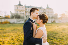 The groom is kissing the beautiful bride in the forehead at the background of the antique gothic castle. during the royalty free stock images