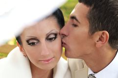 Groom kissing bride Royalty Free Stock Image