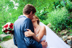 Groom kissing bride. Caucasian adult male groom kissing bride, covering her face Royalty Free Stock Photos