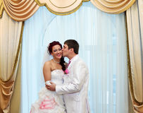 Groom kissing bride on the background of the window Stock Images