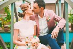 Groom kissing bride on bridge. Happy groom kissing bride on bridge Royalty Free Stock Photos