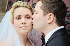 Groom kissing bride on cheek Stock Image