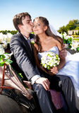 Groom kissing bride in cheek on bench at park Royalty Free Stock Image