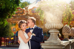 Groom kissing bride in front of carousel in park. Groom kissing bride in front of carousel in summer park Royalty Free Stock Photography