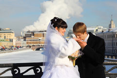 Groom kissing bride hand at winter outdoors. Couple standing on bridge Royalty Free Stock Photo