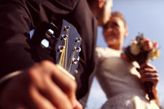 Groom kissing the bride and holding a guitar. Capture of Groom kissing the bride and holding a guitar Royalty Free Stock Photography