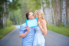 Groom kissing bride holding nameplate Royalty Free Stock Image