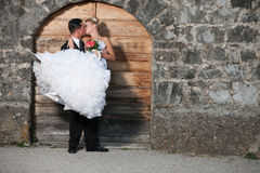 Groom kissing a bride infront of wooden door Royalty Free Stock Photography