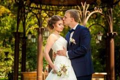Groom kissing bride near arbor in park. Groom kissing bride near decorative pavillion in park Stock Photos