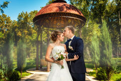 Groom kissing bride near pavillion in park. Groom kissing bride in front of decorative pavillion in park Stock Images
