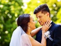 Groom kissing bride outdoor. Groom kissing bride in park Stock Photo