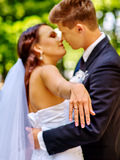 Groom kissing bride. In park outdoor Royalty Free Stock Photos