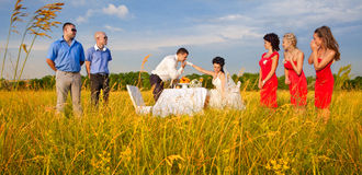 Groom kissing bride`s hand. At wedding table among guests on the field Stock Image