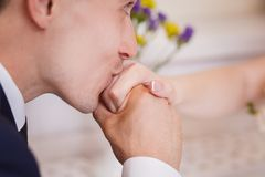 Groom kissing bride's hand Stock Photo